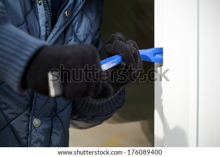 A close up of a burglar trying to open the door - stock photo