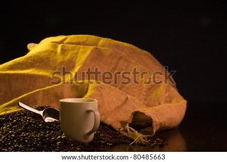 A close up of a burlap coffee bag opened with coffee beans spilling out with a cup of coffee in the foreground. - stock photo