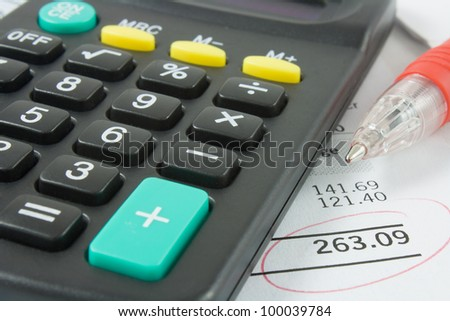 a close up of a calculator and red pen sitting on a bank statement