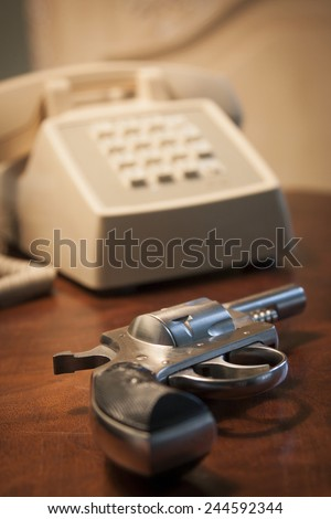 A close-up of a .32 caliber pistol next to a telephone on a brown wooden nightstand table, shallow depth of field. - stock photo
