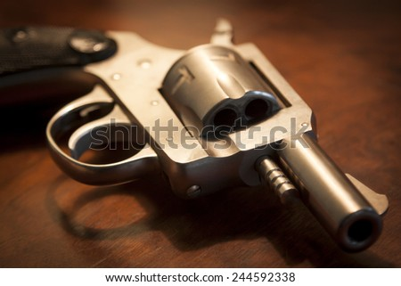 A close-up of a .32 caliber pistol on a brown wooden table, shallow depth of field. - stock photo