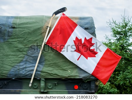 A close up of a Canadian flag attached to a hockey stick hanging on the side of a Canadian Armed Forces military personnel transport truck demonstrating national pride. - stock photo