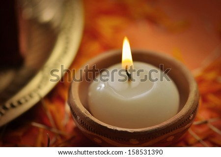 A close up of a candle in an earthen candle-holder - stock photo