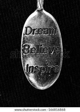 "a close up of a charm with the words ""Dream, Believe Inspire on it.  - stock photo"