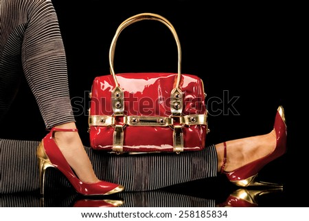 A close-up of a chic red handbag along with sexy female legs wearing elegant red shoes. - stock photo