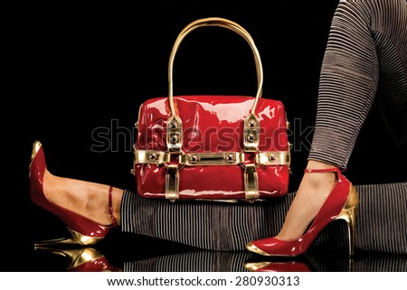 A close-up of a chic red handbag along with sexy female legs wearing elegant red shoes.