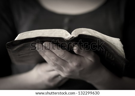A close-up of a christian woman reading the bible. - stock photo