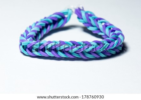 A close up of a colorful rubberband bracelet. - stock photo