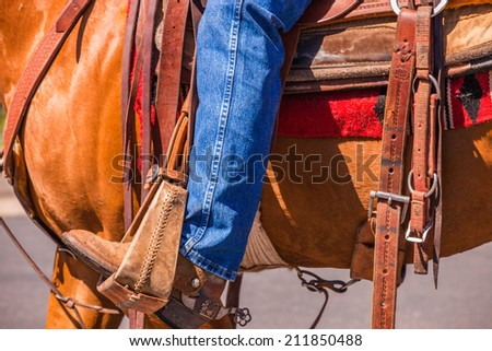 A close up of a cowboy's leg with his boot in the  stirrup. - stock photo