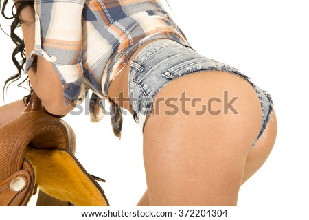 a close up of a cowgirl butt leaning on a saddle. - stock photo
