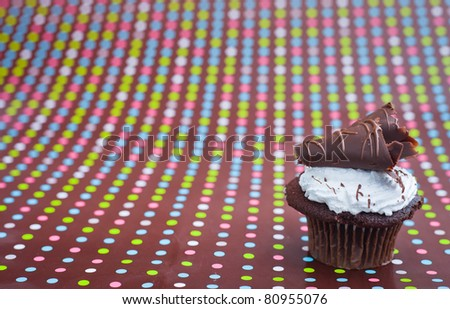 A close up of a dark chocolate cupcake with a polkadot background.