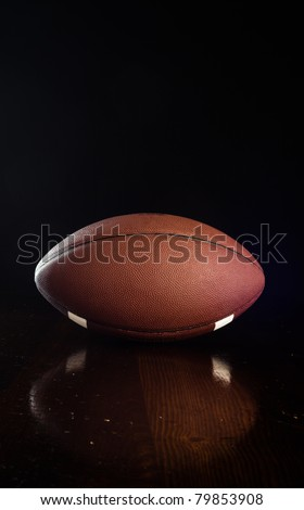 A close up of a football on a wood table. - stock photo