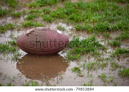 A close up of a football sitting in muddy water and grass. - stock photo