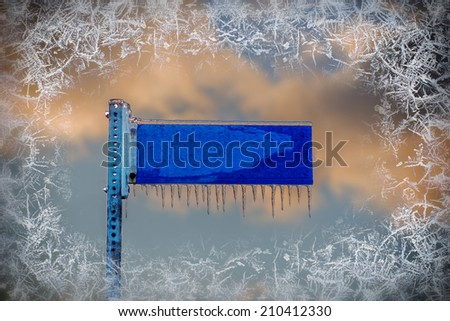 A close up of a frozen blank blue street sign covered in ice and icicles with a frost border surrounding the image.  Room for copy space text.  - stock photo