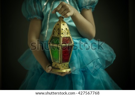 A Close up of a girl holding beautiful decorative Ramadan lantern in hand. Celebration in Holy month of  Ramadan. - stock photo