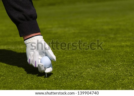 A close up of a golfer with a white glove placing a ball on a tee - stock photo