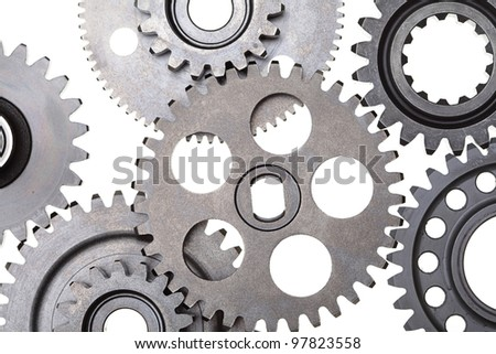A close up of a group of interlocking metal gears. - stock photo