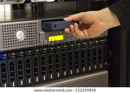 A close-up of a IT engineer / technician insert a backup tape in a backup robot in a rack. Shot in a data center.