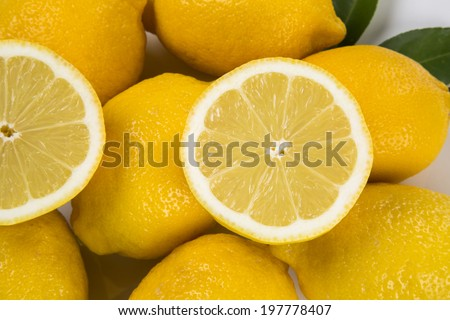 A close up of a lemon cut in a half above some lemons on a white background.