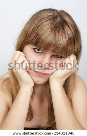 A close-up of a lovely teenage girl with a with a sad facial expression.  - stock photo