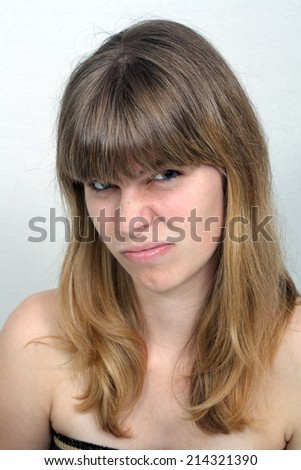A close-up of a lovely teenage girl with a with a skeptical or doubtful facial expression.  - stock photo