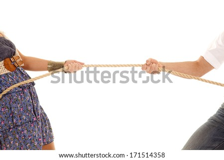 A close up of a man and woman doing a tug of war with a rope. - stock photo