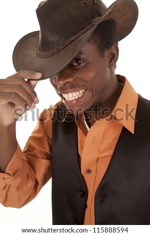 A close up of a man in his cowboy hat and vest with a big smile. - stock photo