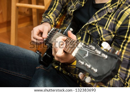 A close up of a man's hands playing the guitar. - stock photo