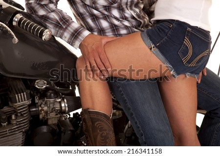 a close up of a man sitting on a motorbike with a woman's legs on his leg. - stock photo
