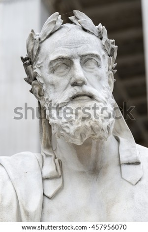A close up of a marble greek statue adorned with a laurel leaf outside the parliament building in Vienna Austria.