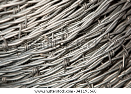 A close-up of a reel of barbed wire and fencing material.