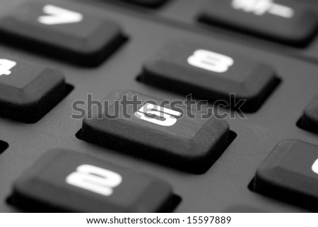 A close up of a rubber keypad of a calculator focused on number 5.