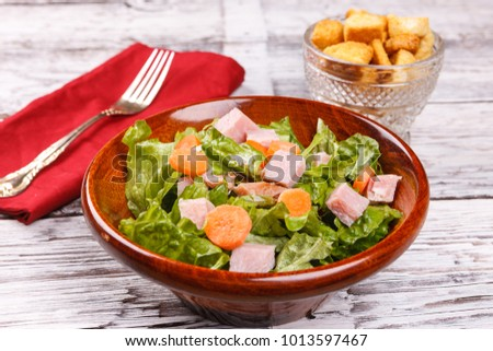 A close up of a salad with bits of ham and carrots.
