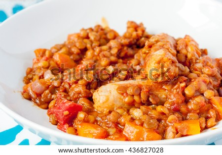 A close-up of a sausage and lentil casserole in a white bowl - stock photo