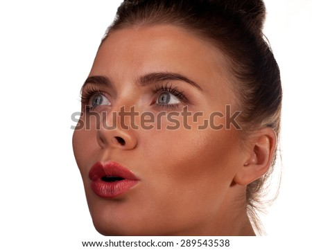 A close up of a shocked woman face with natural skin on isolated background. - stock photo