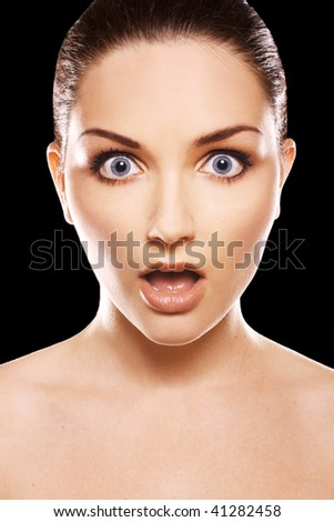 A close up of a shocked woman in front of a black background.