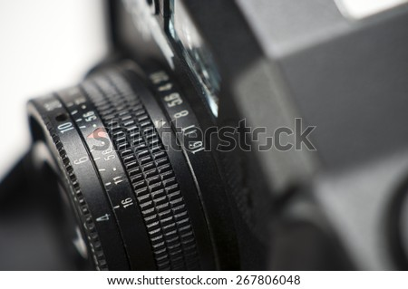 A close up of a small camera lens in a old film camera - stock photo