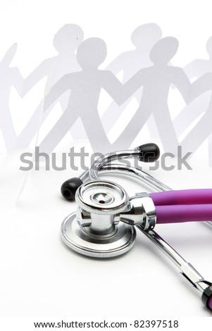 A close-up of a stethoscope and paper people, isolated on white - stock photo