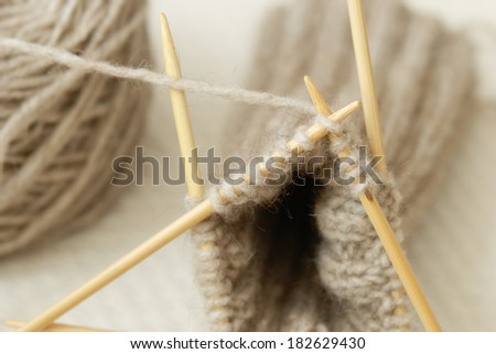 A close up of a stitch being made in the cuff of a hand-knitted sock on four needles from natural fiber yarn