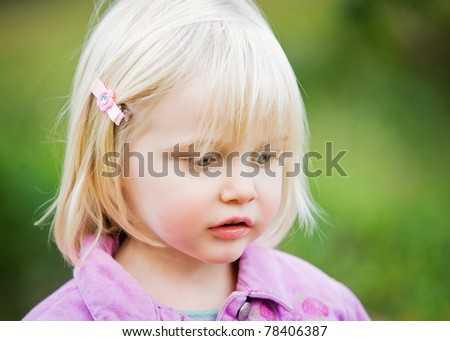A close-up of a sweet little girl with beautiful features.  The little girl has blond hair, blue eyes and long eye-lashes.  She is looking to the side with a curious, relaxed look on her face. - stock photo