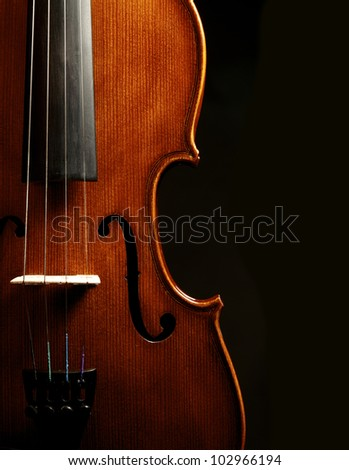A close up of a syphony violin set against a black background