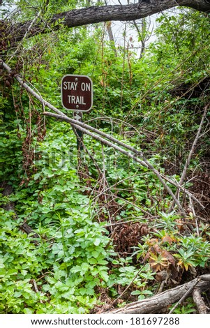"A close up of a trail sign that says ""stay on trail"" covered in plants. - stock photo"