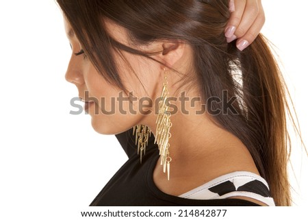 A close up of a woman holding up her hair wearing dangle earrings.