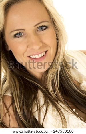 a close up of a woman in her wedding dress looking with a smile.