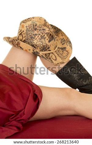 a close up of a woman laying under a red sheet with a cowboy hat on her knee. - stock photo