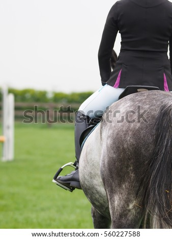 A close up of a woman riding a horse away from the camera.