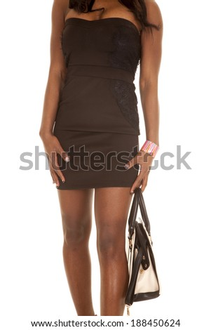 A close up of a woman's body holding on to her purse. - stock photo