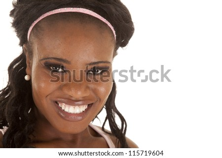A close up of a woman's face with a pink head band and a smile. - stock photo