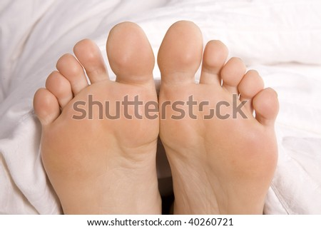 A close up of a woman's feet coming out of the covers.