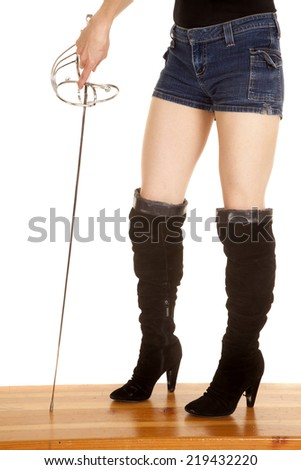 A close up of a woman's legs wearing knee high boots, holding on to a pirate sword. - stock photo